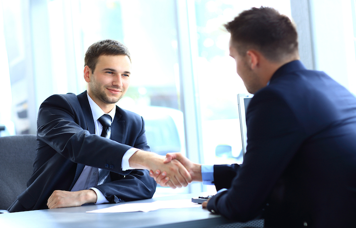 Two businessmen shake hands in agreement. Combine marketing and branding with authentic human interactions to be successful.